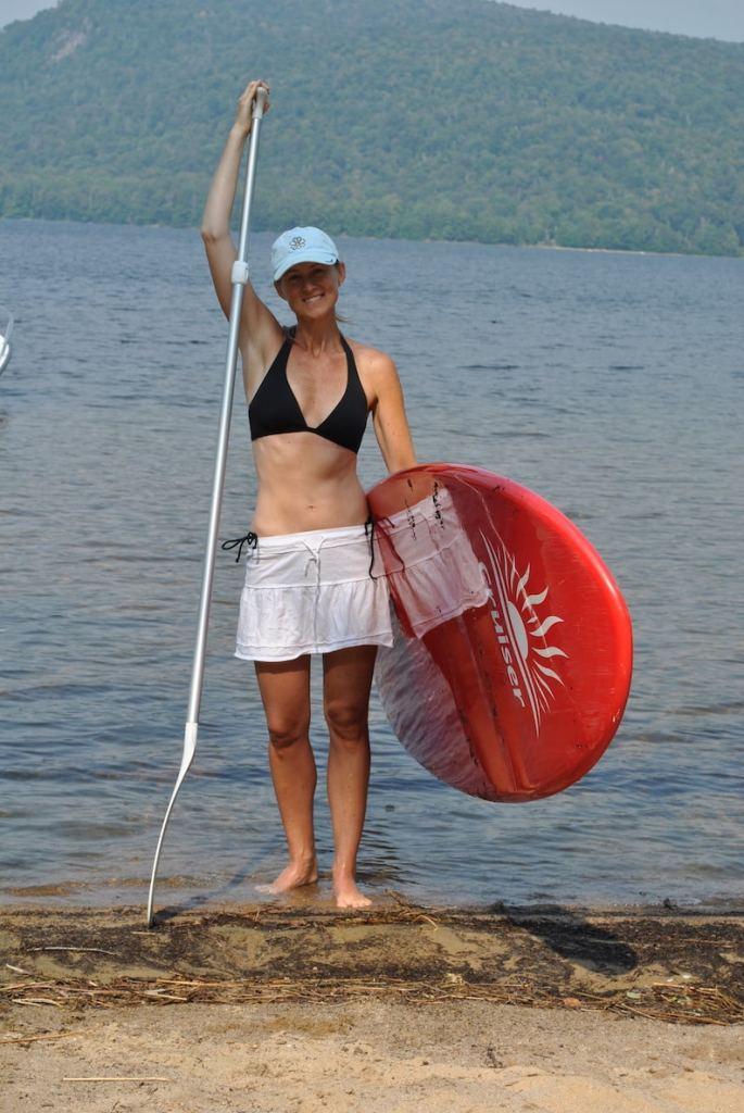 Kellie Logsdon finally healthy.  Wearing black bikini, white skirt holding red surfboard and tall silver oar.
