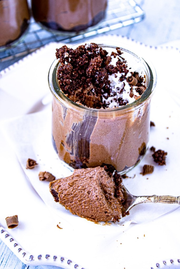 Close up of small glass jar with Chocolate cheesecake inside. Silver spoon with brown chocolate creamy mixture on spoon. White background.