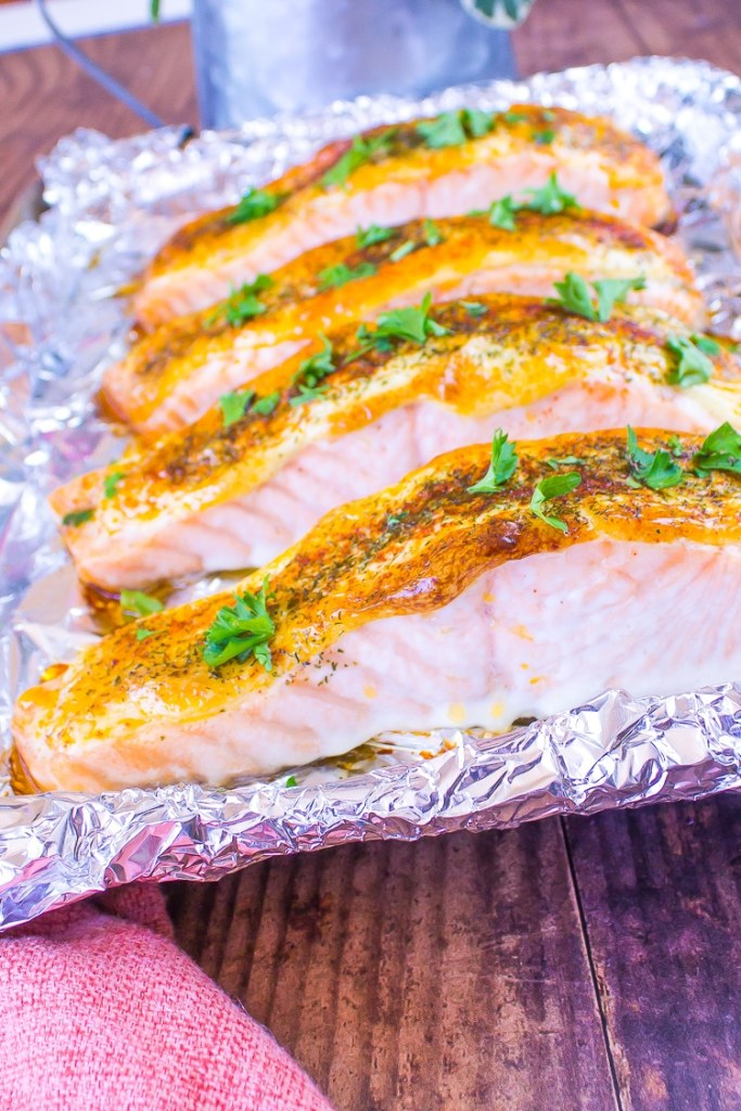 Baked pink Dijon Salmon filets on a foil lined baking sheet. Green parsley sprinkled on top.