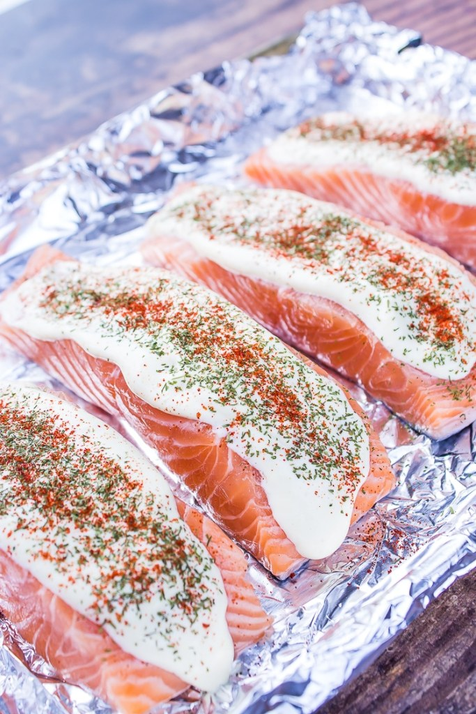 4 raw salmon filets on shiny tin foil. Tops smeared with light yellow dijon mayo mixture.Then sprinkled with dill and orange paprika.
