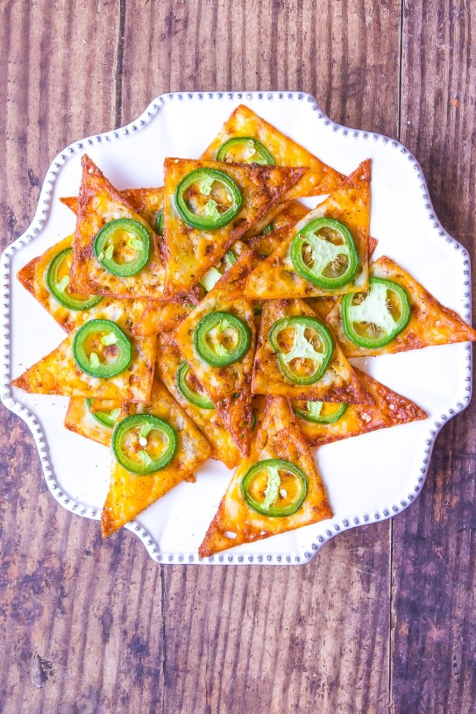 A plate of stacked chips called Keto Doritos. Dark orange triangles with green round slice of jalapeno baked.