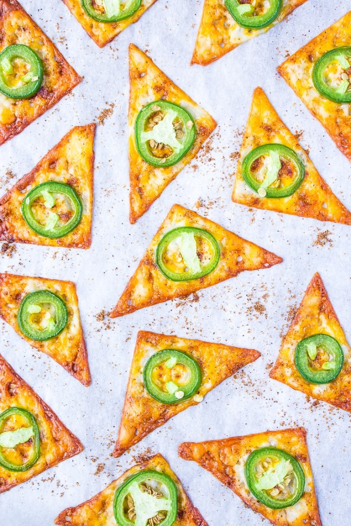 Baking sheet with baked orange triangles. Green round jalapeno on each triangle. Dark orange season salt sprinkled over the tray.