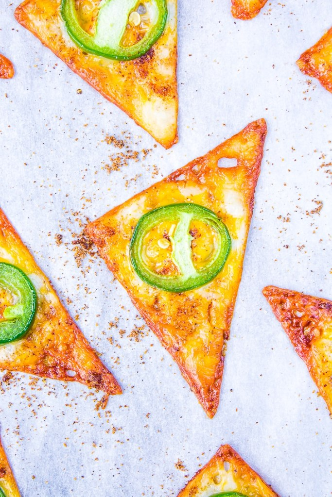 Orange and light brown triangles of cooked cheese with a green slice of jalapeno baked on top.