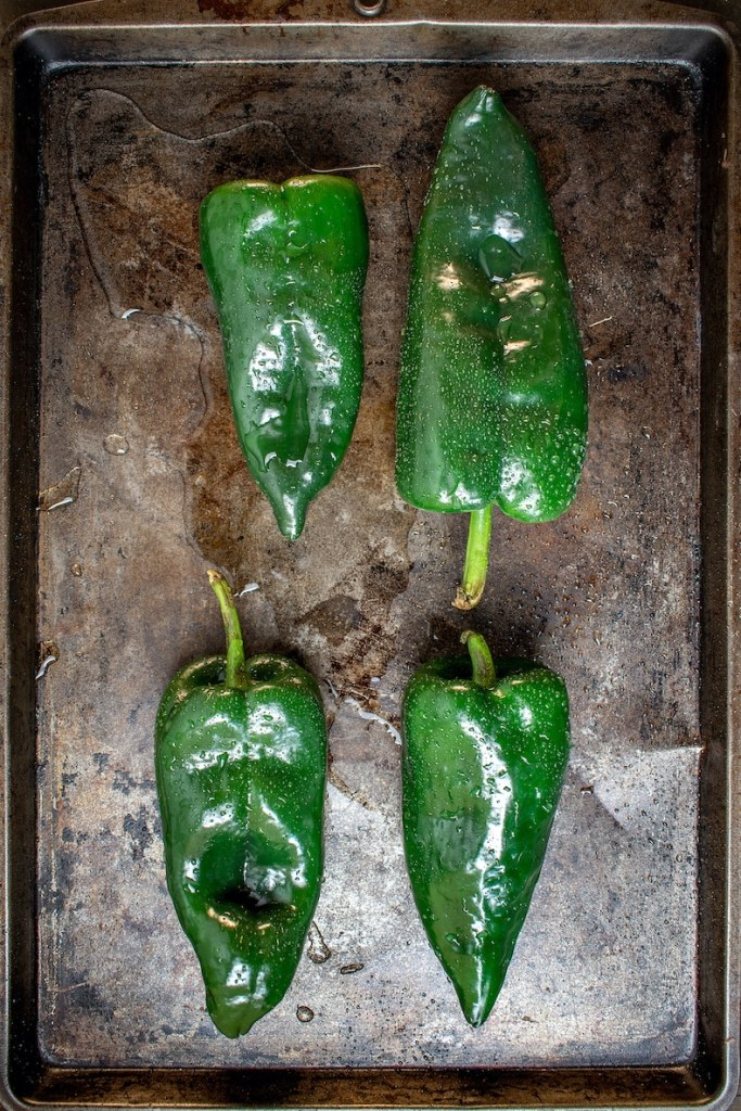 Fresh Poblano peppers on dark baking sheet