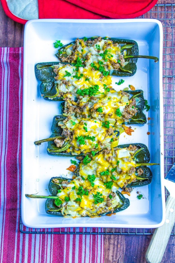 White rectangle casserole dish on top of a red and white striped towel.  Four dark green poblano pepper chiles stuffed with a meat mixtures and topped with orange melted cheese and green parsley.