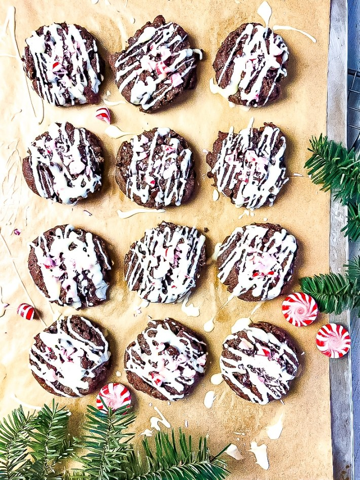 Top down view of 12 chocolate cookies lined up on a cookie sheet on parchment paper.  Brown cookies are sprinkled with crushed red and white candy and then drizzled with white frosting. Green evergreen sprigs are places at edge of cookie sheet.