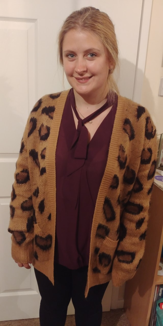 Women standing wearing a leopard print cardigan over a burgundy blouse.