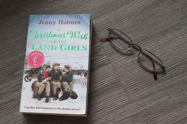 Front cover of a christmas wish for the land girls with a pair of reading glasses.