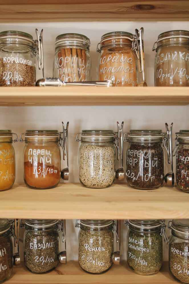 variety of spices organised in glass jars on wooden shelves