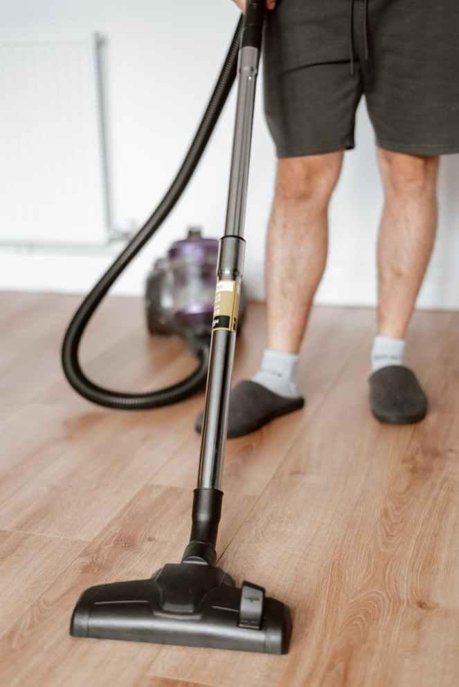 man vacuuming floor with cleaner in home, keeping it organised.