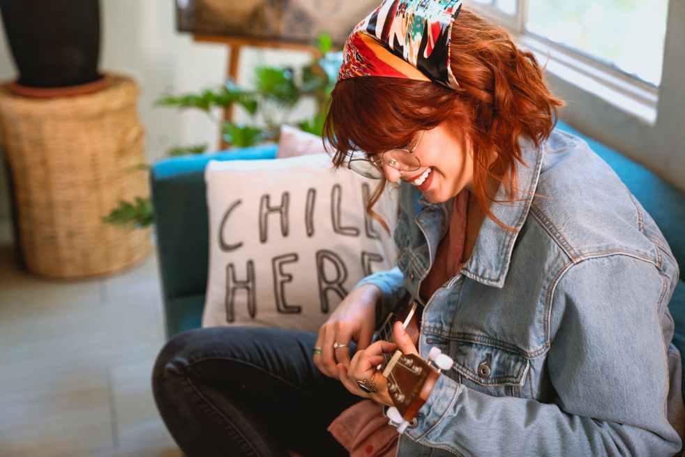 woman in light blue denim jacket playing her ukulele