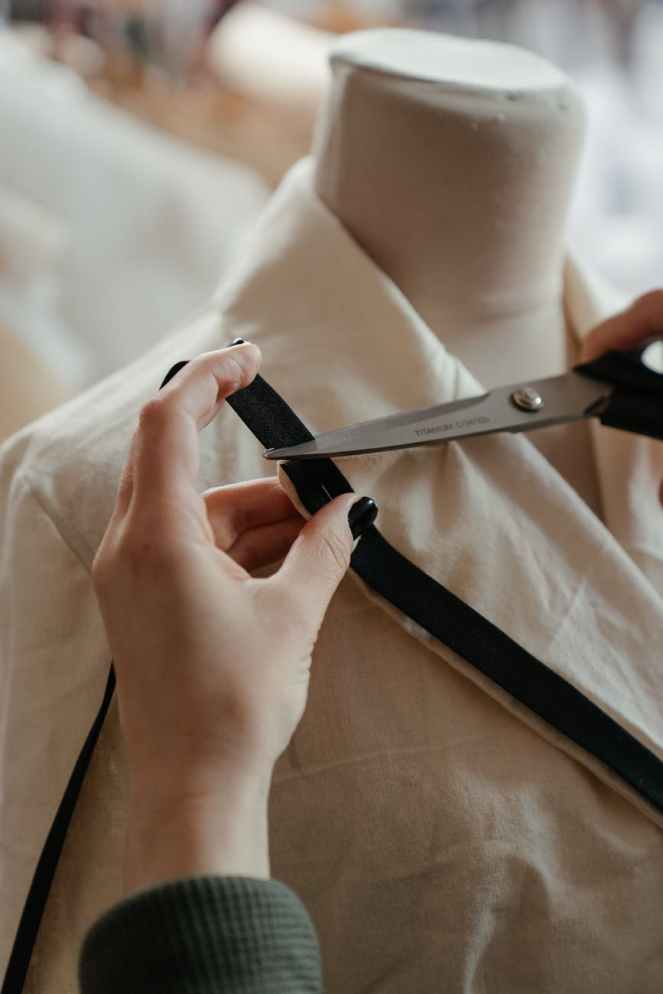 person in white button up shirt holding black leather belt for introducing Violet's Vintage post