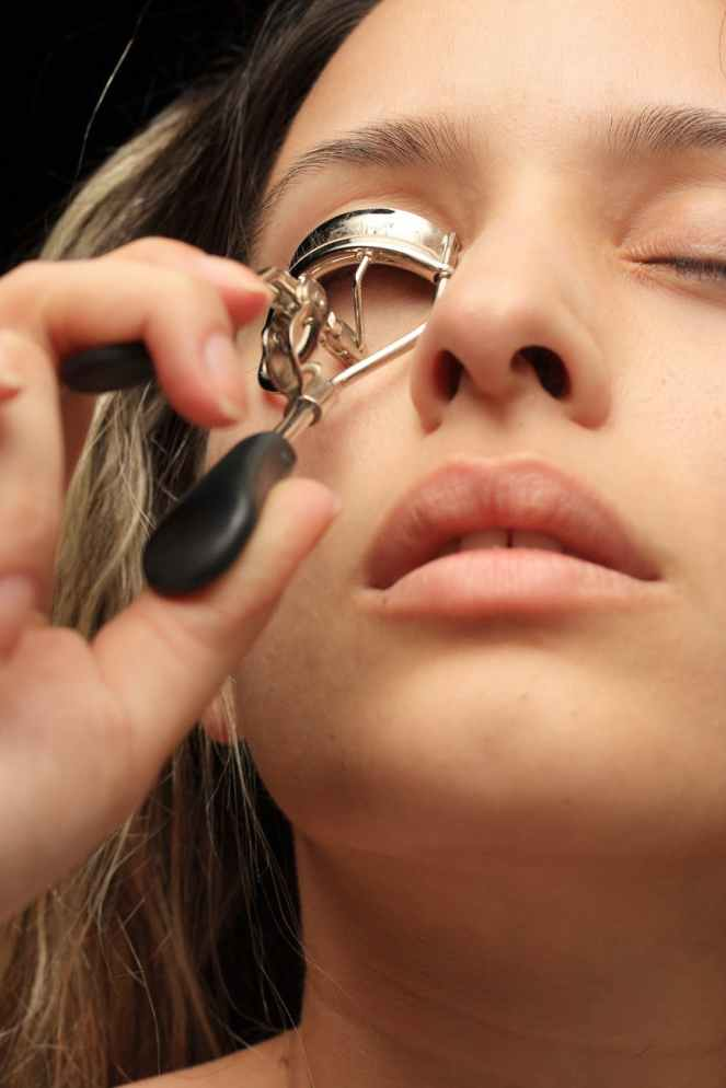 woman using eyelash curler close up photography for bespoke lashes post