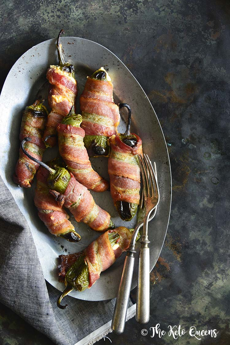 Keto Bacon Wrapped Jalapeno Poppers on a silver tray with 2 forks on a dark background