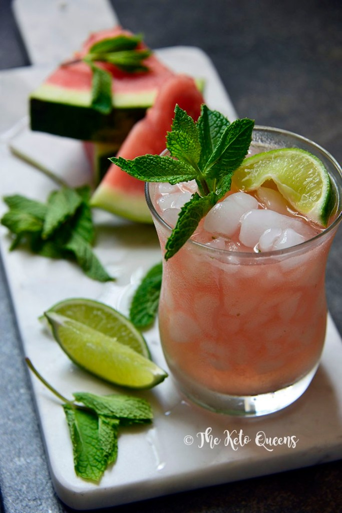 low carb watermelon mojito in a glass with lime and mint on a white tray