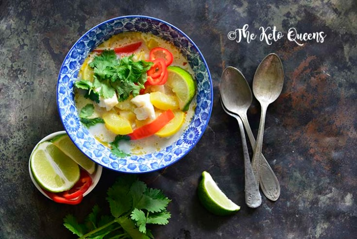 Horizontal image of a bowl of thai coconut curry with red bell peppers and yellow squash.