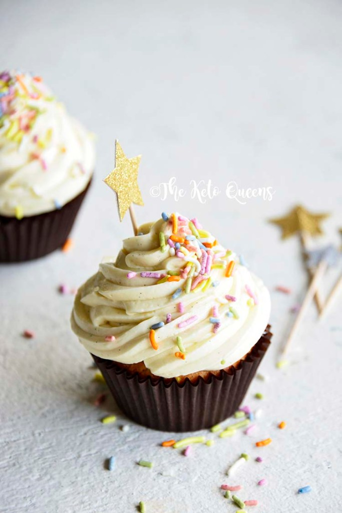 vertical image of a keto cupcake - vanilla cupcake with white chocolate buttercream frosting with sprinkles and a star