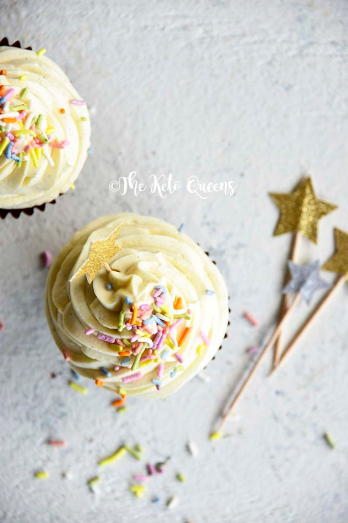 vertical overhead image of a keto cupcake - vanilla cupcake with white chocolate buttercream frosting with sprinkles and a star