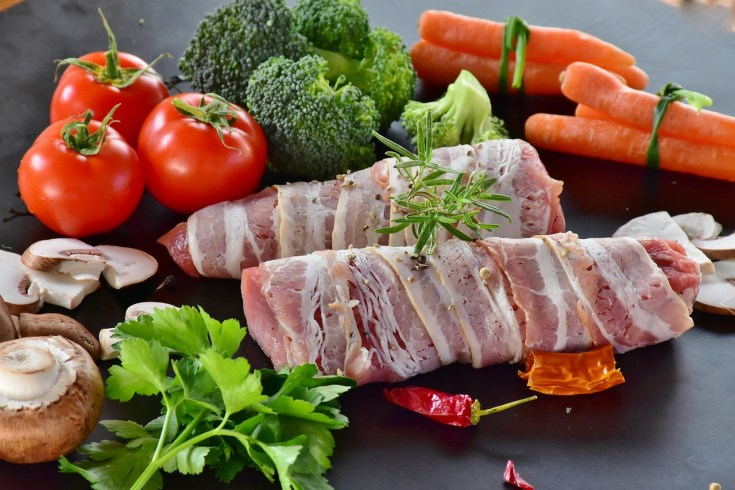 bacon wrapped meat with fruit and vegetables around it