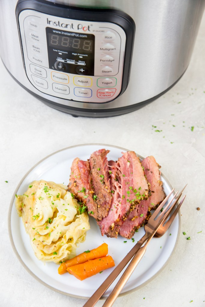 vertical image of corned beef, cabbage and carrots on a white plate with rose-colored fork and knee with napkin and instant pot halfway in frame