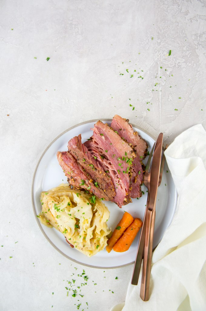 zoomed out vertical image of corned beef, cabbage and carrots on a white plate with rose-colored fork and knee with napkin