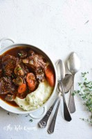 vertical image of low carb instant pot beef stew in a white bowl with 3 spoons and fresh herbs on a white background