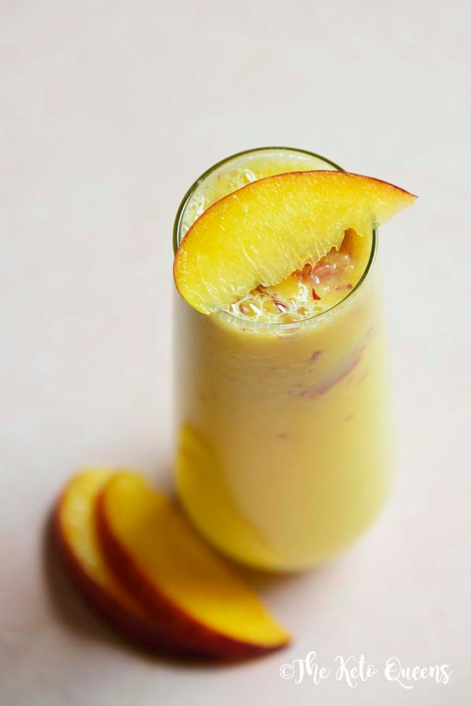 low carb peach bellini mocktail in a seamless glass with peaches on top