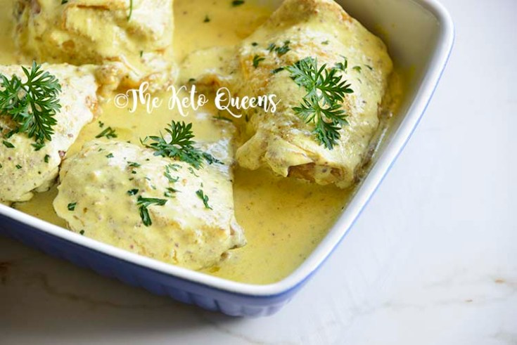 Roasted Chicken Thighs with Creamy Mustard Sauce in a blue and white casserole dish sprinkled with parsley