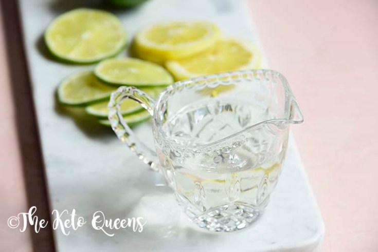 keto simple syrup in a glass with lemons and limes on a marble slate
