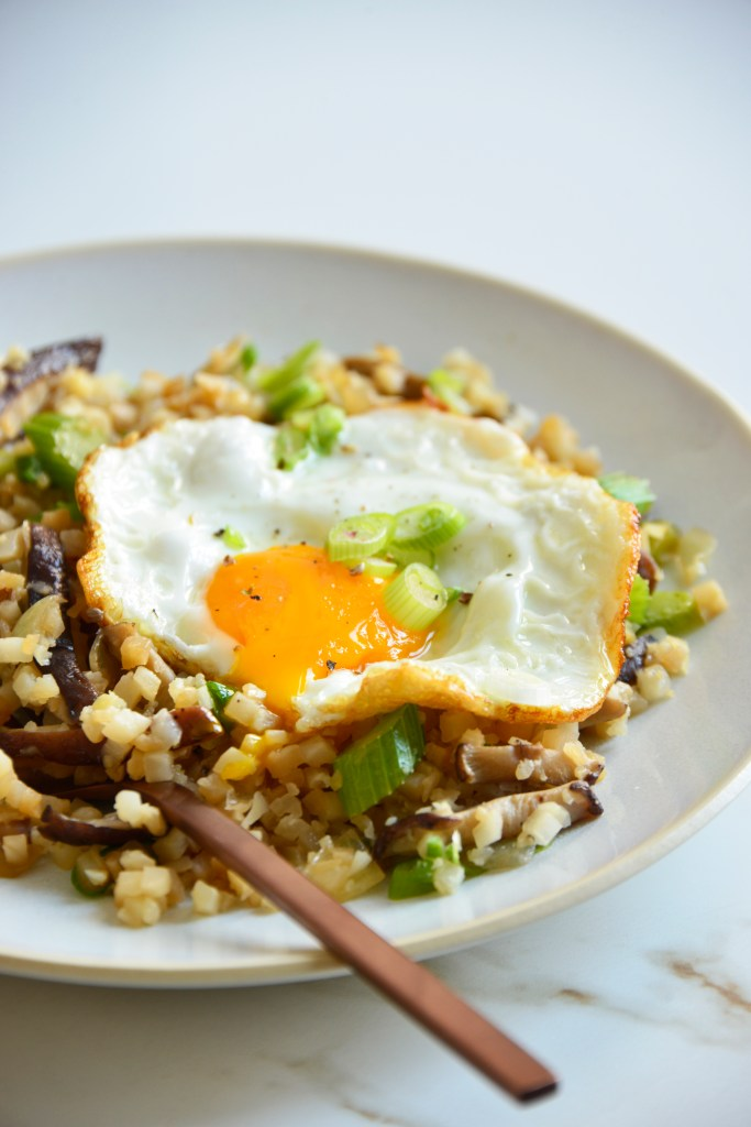 cauliflower fried rice on plate topped with an egg
