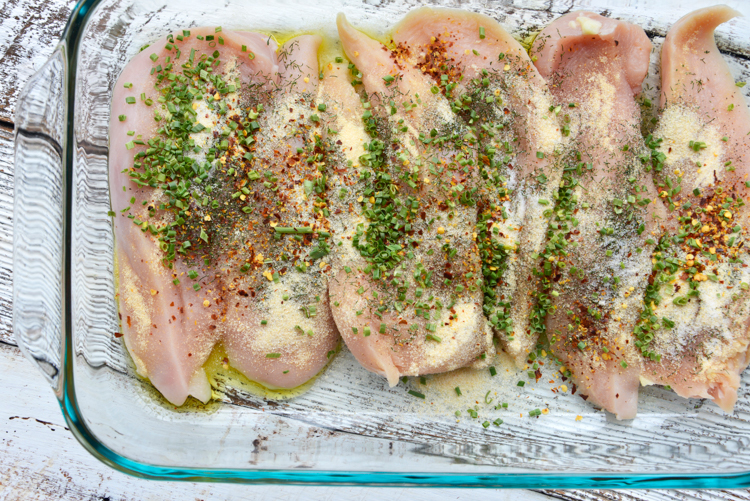 seasoned raw chicken in glass baking dish