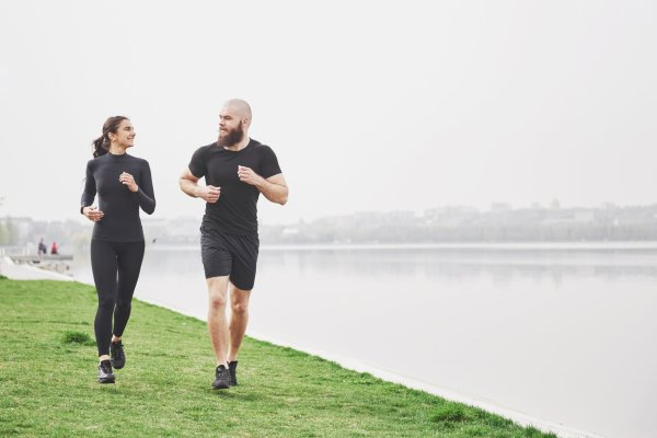Couple jogging and running outdoors in park near the water. Young bearded man and woman exercising together in morning