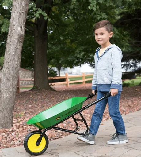 kid pushing a green wheelbarrow