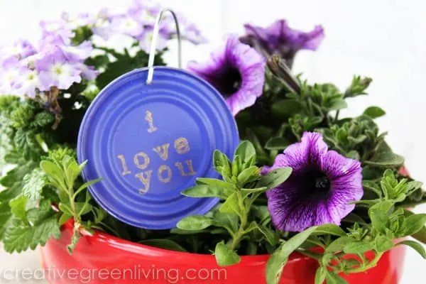 Purple garden marker hanging in a pot of petunias