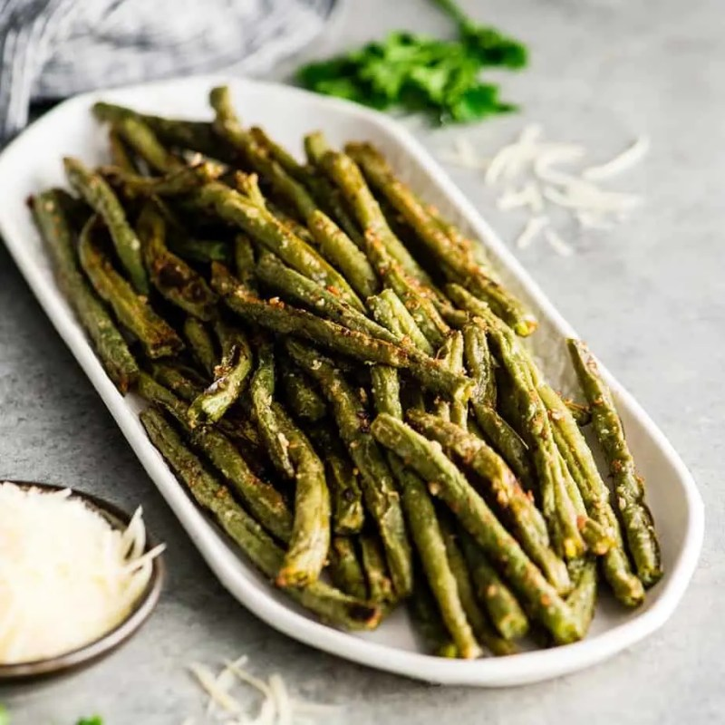 roasted green beans on a white platter