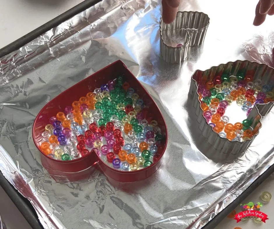 Metal heart cookie cutters on aluminum foil covered pan. Cutters are being filled with colorful pony beads.