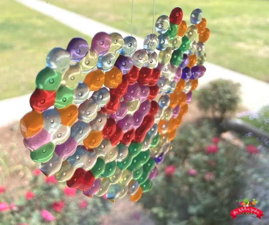 Pony bead sun catcher hanging in a large window with shrubs and grass in the background.