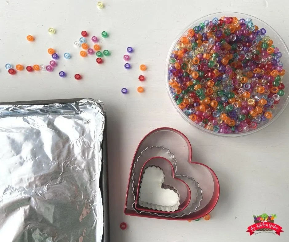 bowl of pony beads, metal heart cookie cutters, and a foil covered sheet pan on a white table