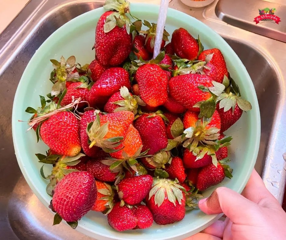 bright red strawberries in light green colander.