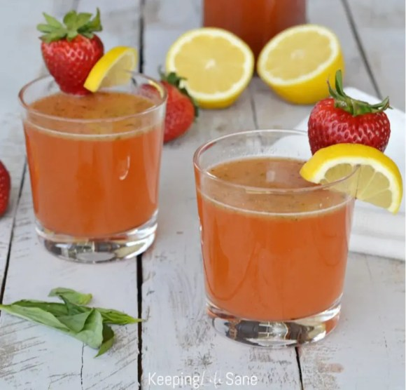 strawberry lemonade mimosas in clear glasses garnished with a lemon slice and strawberry
