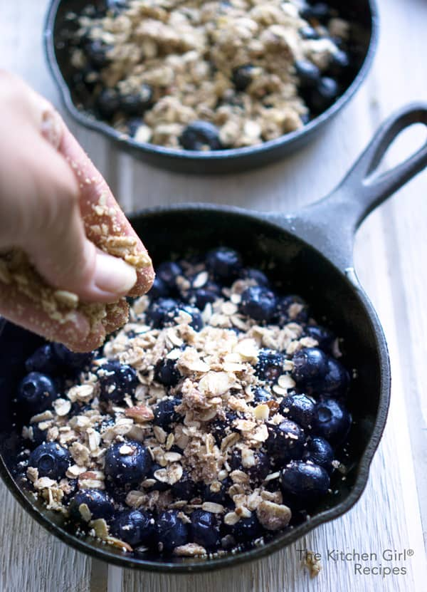 Fresh (or frozen) blueberries baked with a crisp, oat and almond topping. Gluten free, vegan Blueberry Crisp recipe at thekitchengirl.com #blueberrycrisp #blueberries #summer #fruitcrisp #berrycrisp #glutenfree #vegan #almondmeal