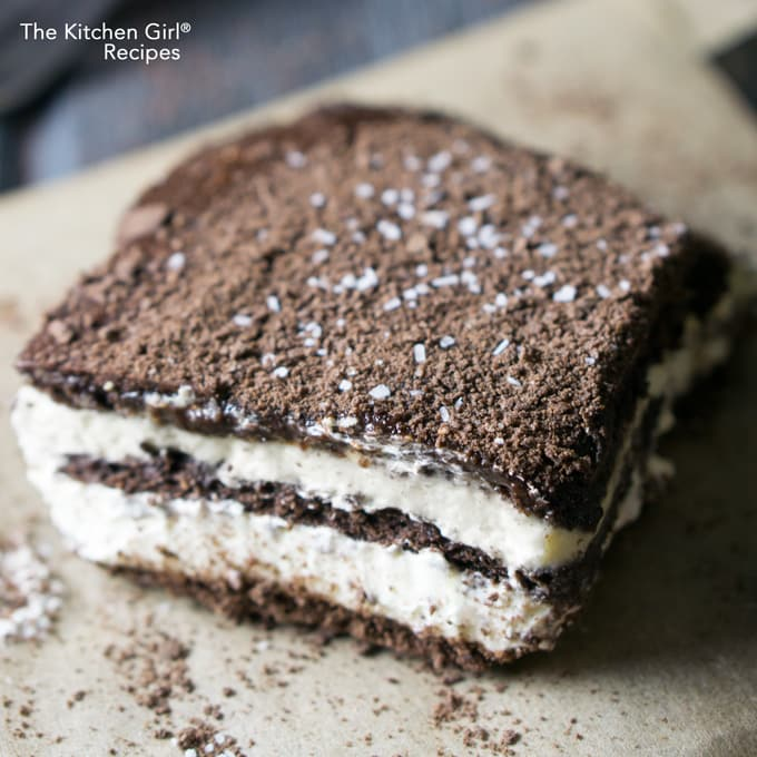 Easy, no bake refrigerator dessert! Icebox Chocolate Eclair Cake has chocolate grahams, chocolate topping, and flecks of Kosher salt! thekitchengirl.com #refrigeratorcake #sexinapan #nobakedessert #gameday #gamedaydessert #summerdessert #chocolate #puddingcake