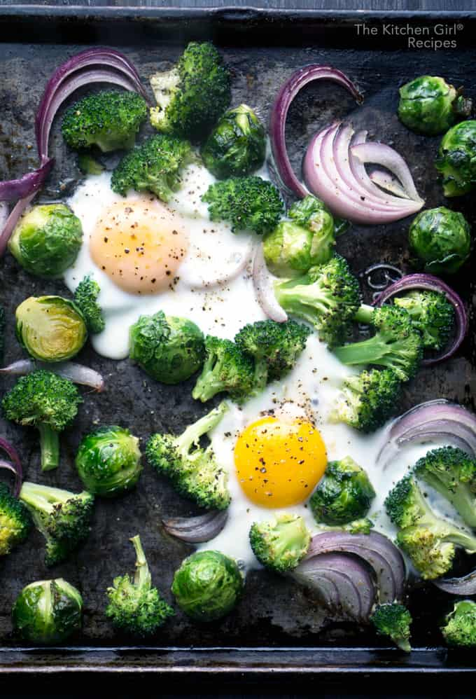 Hands-free, 20 min eggs with ALL the veggies! Sheet Pan Baked Eggs Brussels Sprouts and Broccoli with red onion is baked not fried on thekitchengirl.com #bakedeggs #sheetpanbreakfast #sheetpanmeal #roastedvegetables #breakfast #healthybreakfast #brusselssprouts #bakednotfried #paleo