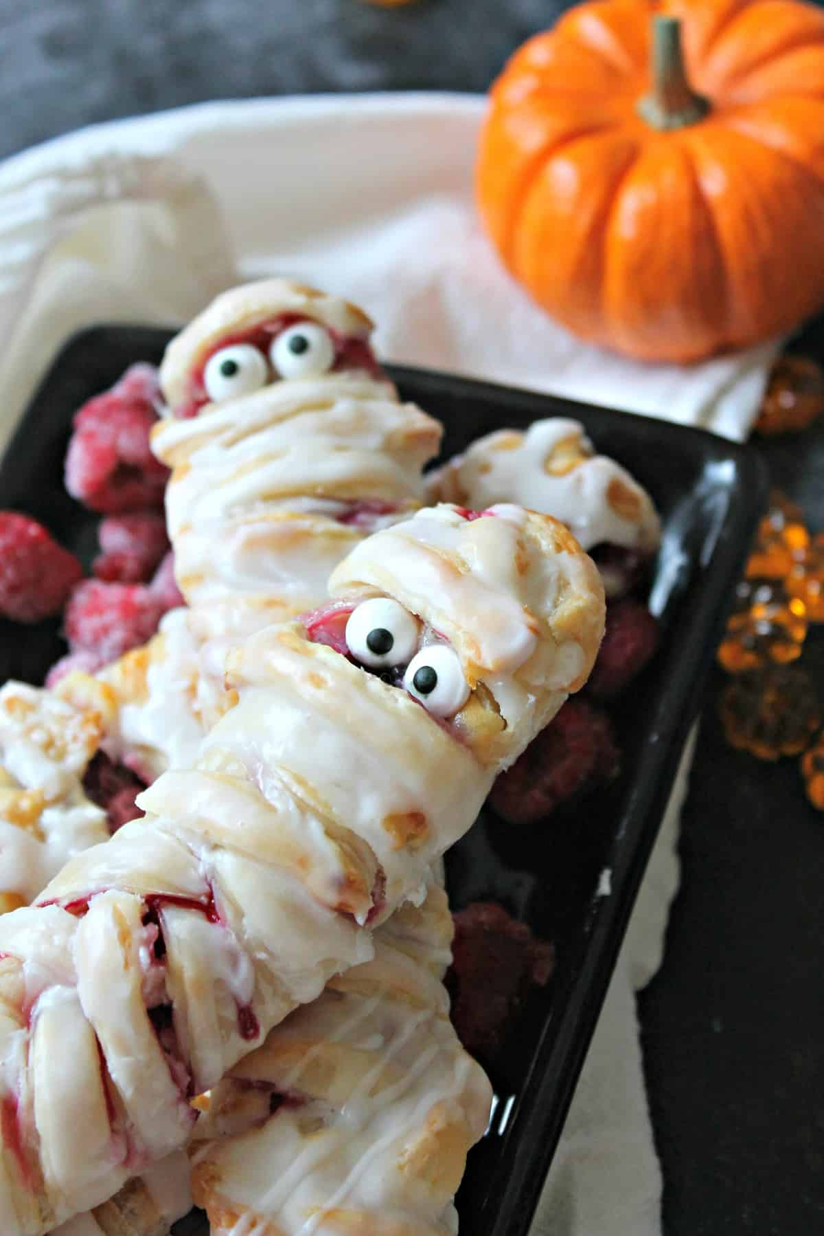 Berry & Cheese Danish Mummies are the perfectly sweet and spooky way to start off your Halloween! Store bought puff pastry makes these a cinch to create!