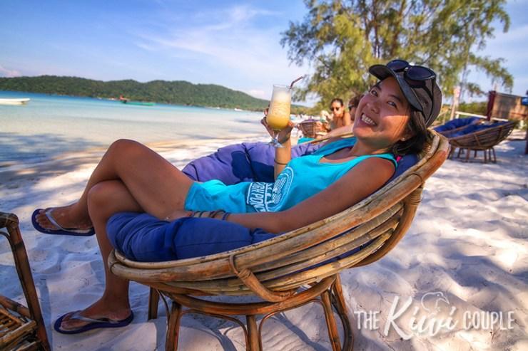 Rachel relaxing on a beach in Cambodia, drink in hand.