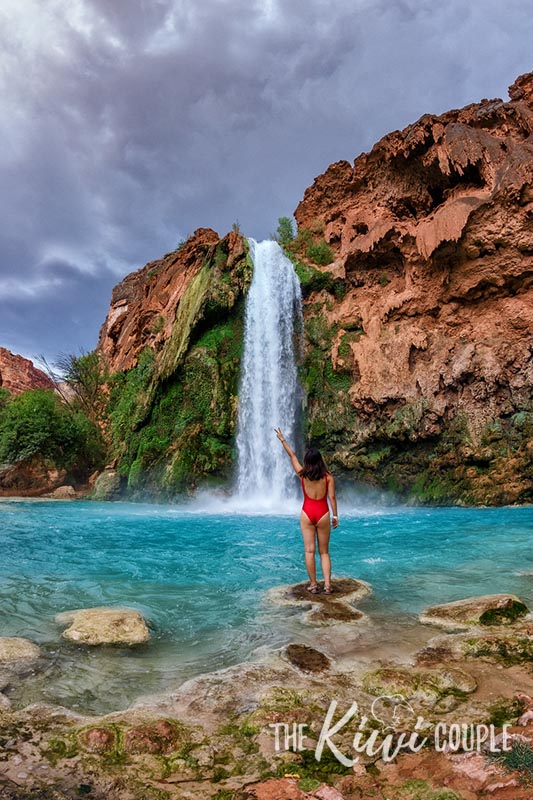 Rachel in a red swimsuit standing in front of the blue Havasu Falls, in the Grand Canyon