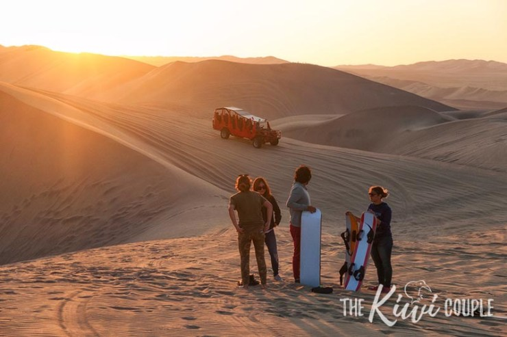 A group of people with sand boards, standing on sand dunes watching the sunset. A dune buggy is in the background.