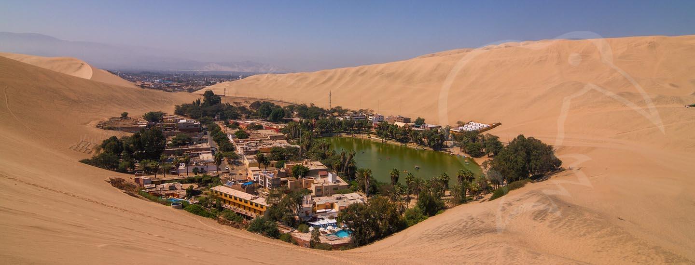 Sand dunes surrounding a desert oasis in Peru