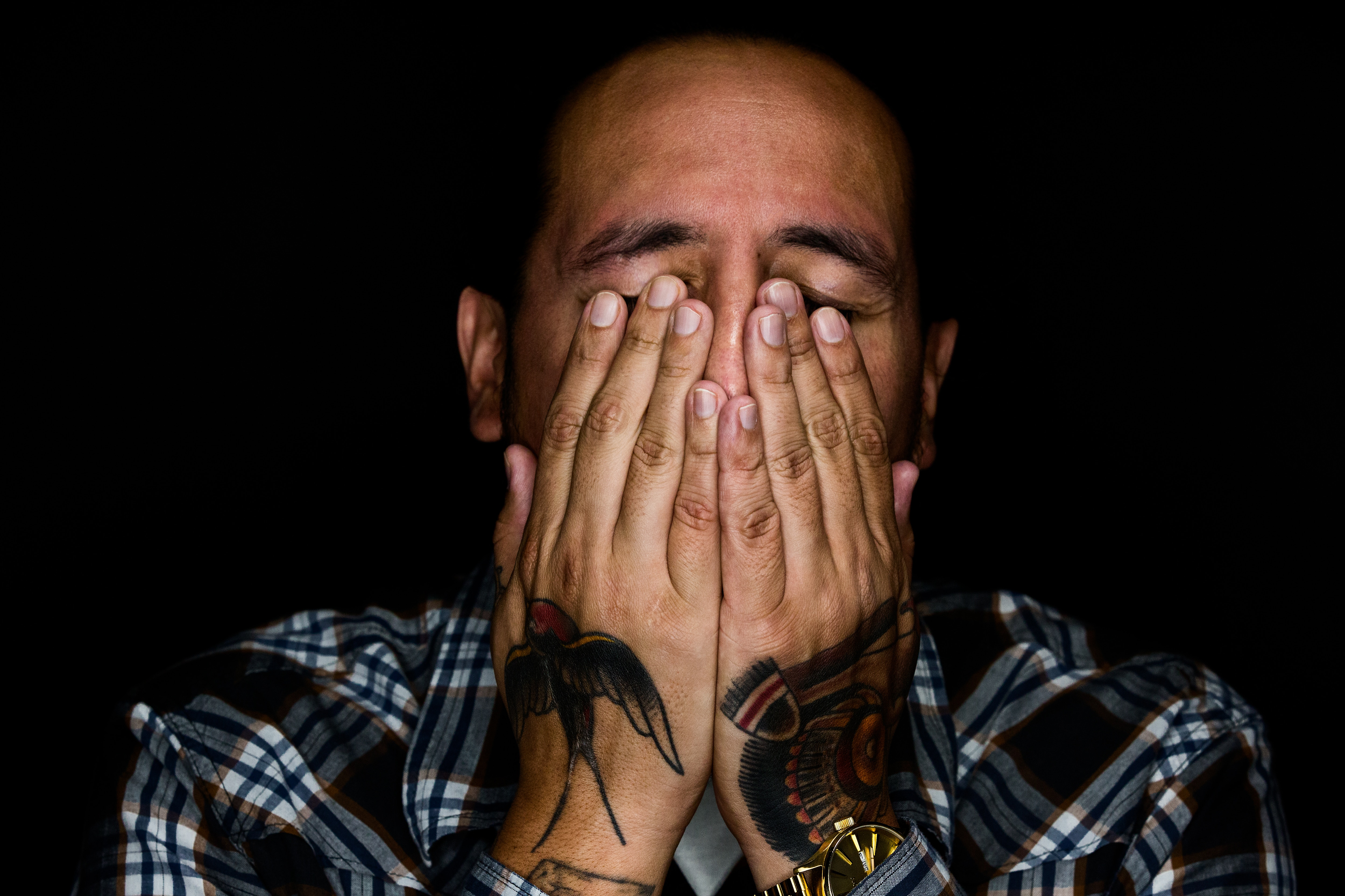 A man with tattoos on his hands covers his face in consternation. He's wearing a blue flannel shirt.