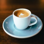 A macchiato in a white cup sits on a white sauces on a wooden table. It has a dollop of foam on top and is about 3 ounces.